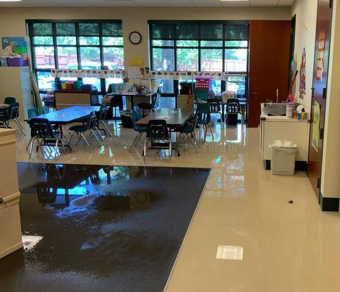 flooded children's classroom. The carpet and tile flooring is wet from a water leak.