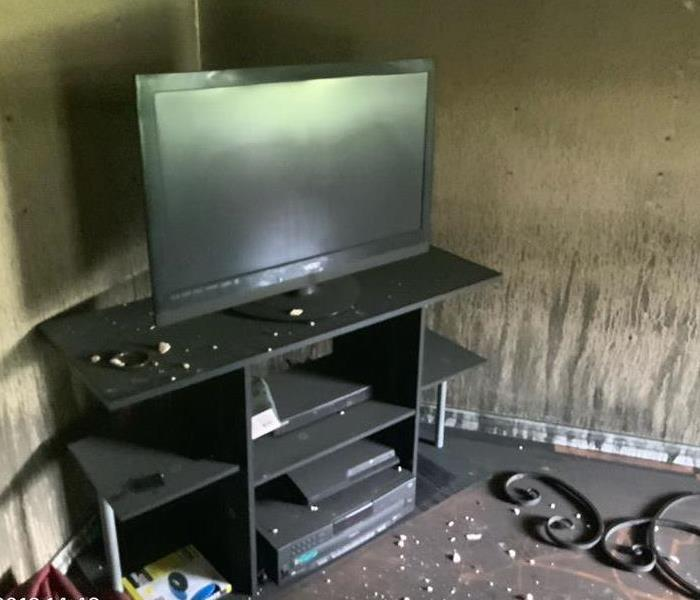 TV and a tv stand the surrounding areas covered in smoke and soot residue.