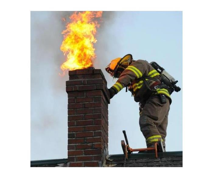 Fire fighter inspecting a home chimney fire.