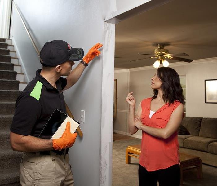A SERVPRO professional providing a detailed explanation of services to a customer.