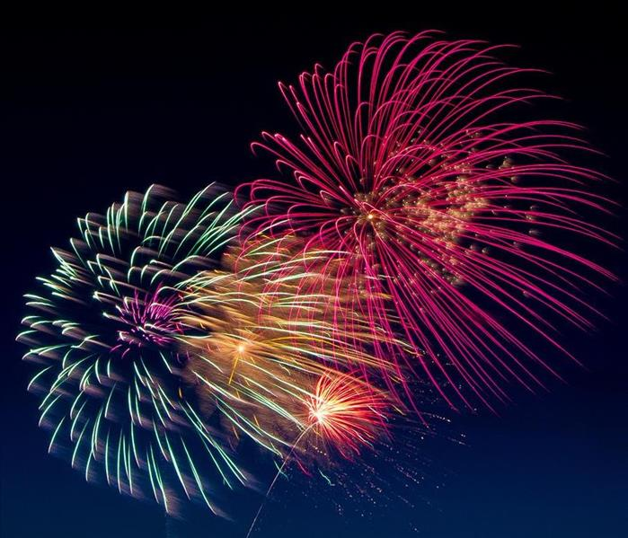 Fireworks of red, yellow, orange, green, and purple in the night sky.